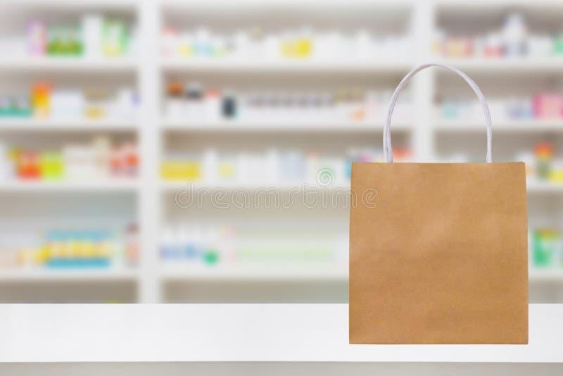 Sacco di carta sulla tavola del contatore della farmacia della farmacia con il prodotto di sanità e della medicina fotografia stock libera da diritti