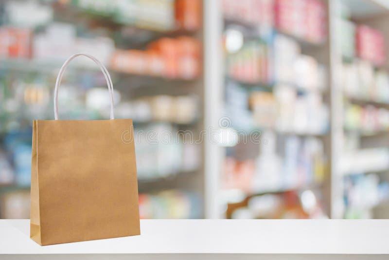 Sacco di carta sulla tavola del contatore della farmacia della farmacia con medicina fotografia stock