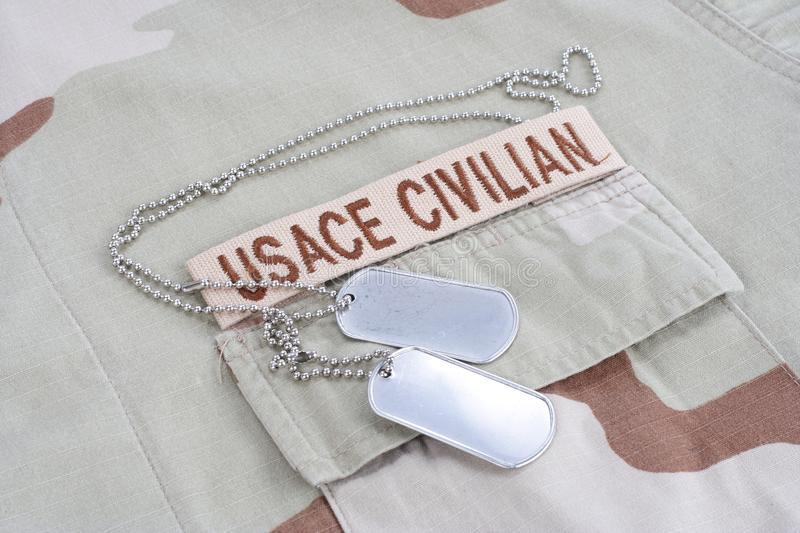 SACE CIVILAN branch tape with dog tags on desert camouflage uniform. USACE CIVILAN branch tape with dog tags on desert camouflage uniform background stock images