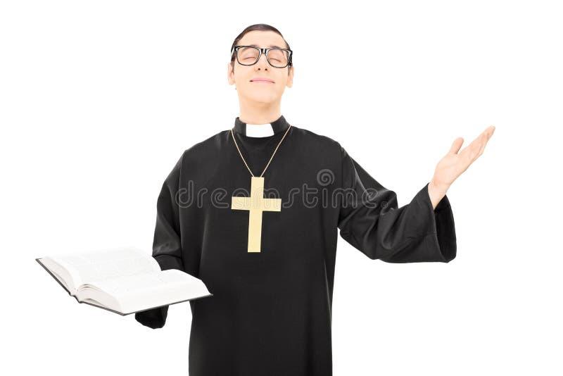 Sacerdote alegre joven que ruega a dios fotografía de archivo