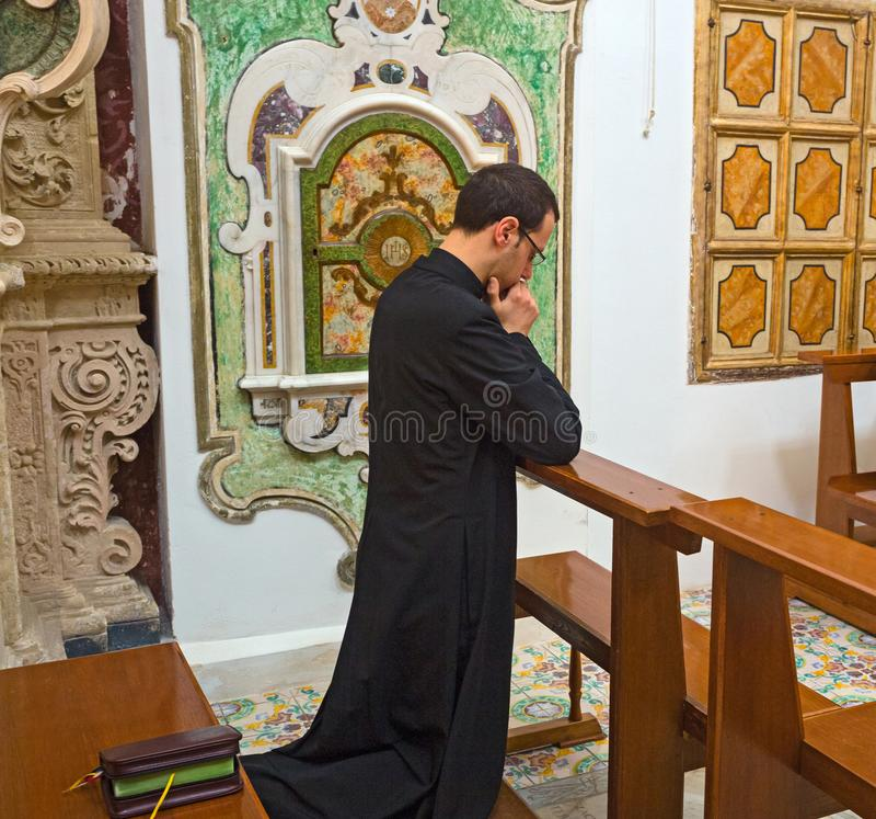 Sacerdote católico joven que se arrodilla en rezo foto de archivo libre de regalías