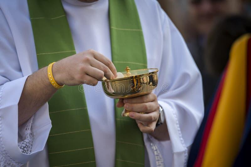 Sacerdote católico que dá a um protetor suíço o comunhão santamente foto de stock royalty free
