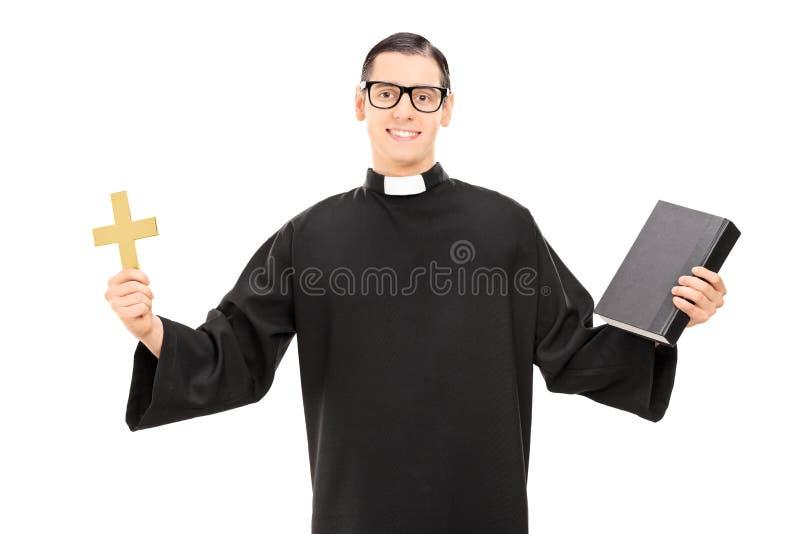 Sacerdote católico que lleva a cabo la Sagrada Biblia y una cruz de oro fotos de archivo