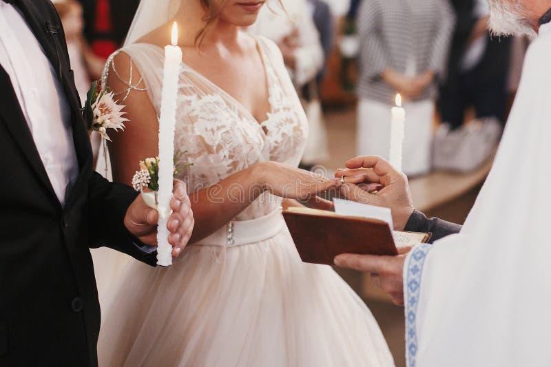 Sacerdote che mette sulla fede nuziale dorata sul dito della sposa Nozze m. fotografia stock libera da diritti