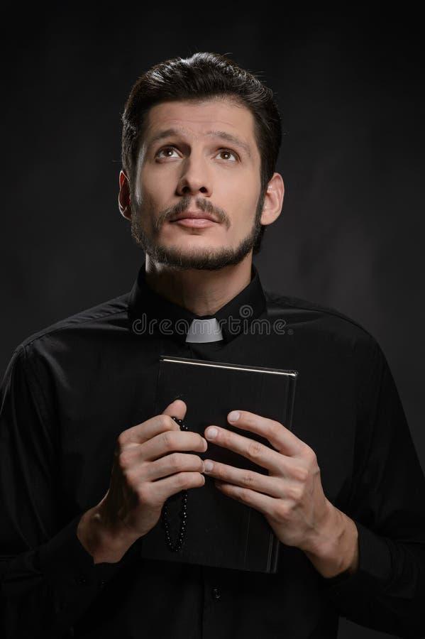 Sacerdote con la Sagrada Biblia. Retrato del sacerdote que sostiene el santo imagen de archivo