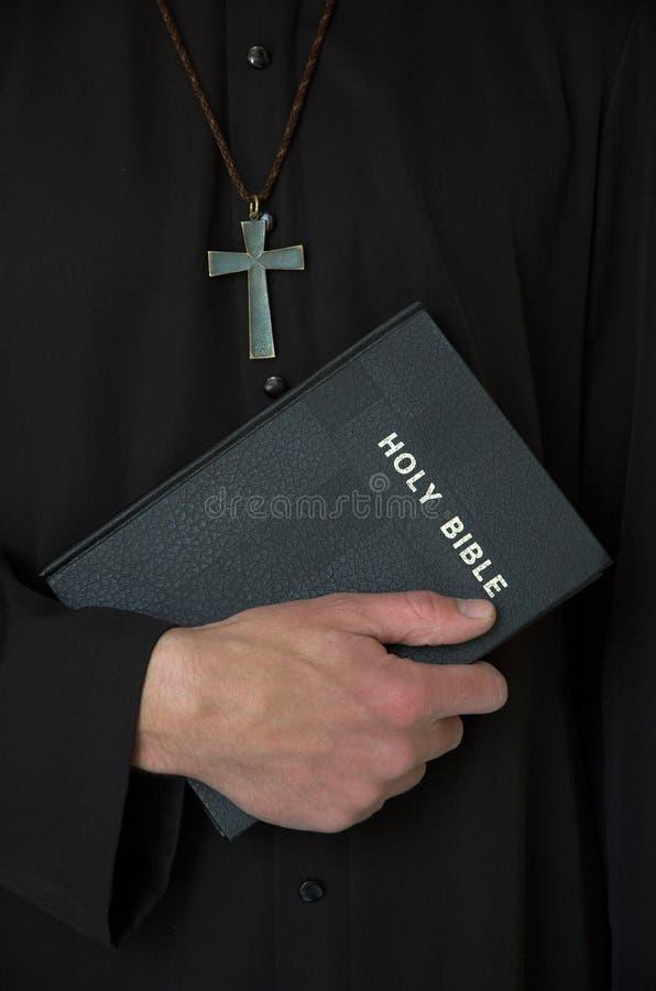 Sacerdote, cruz y biblia imagen de archivo