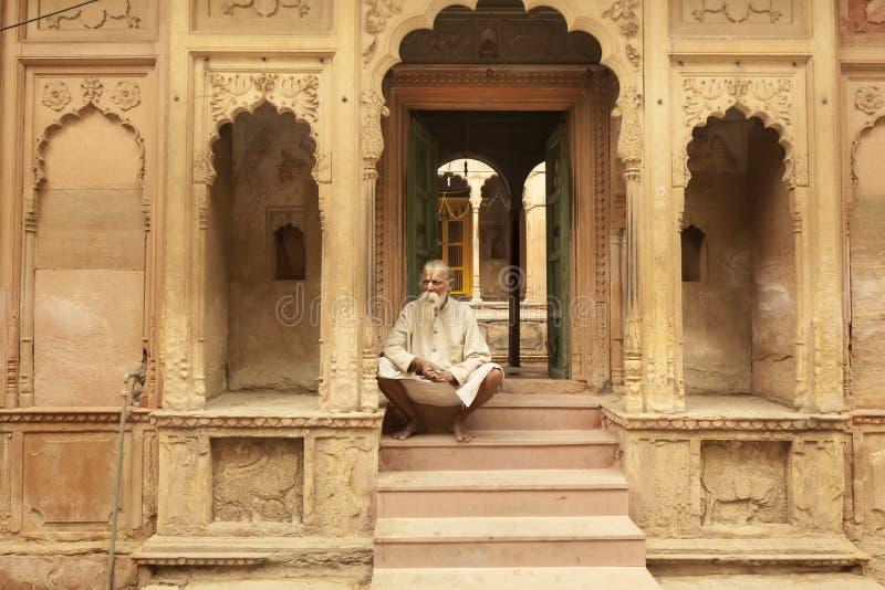 Sacerdote de sexo masculino que se sienta cerca del templo antiguo en Vrindavan la India imagen de archivo