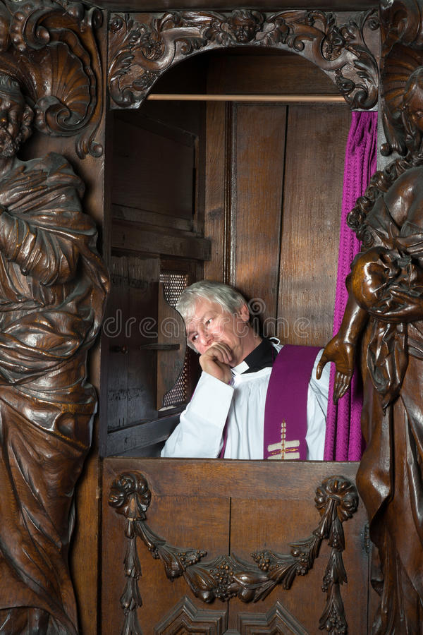Sacerdote en cabina de la confesión foto de archivo