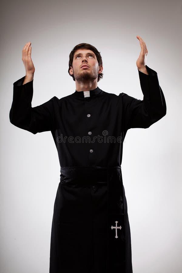 Sacerdote que aumenta las manos y que ruega foto de archivo