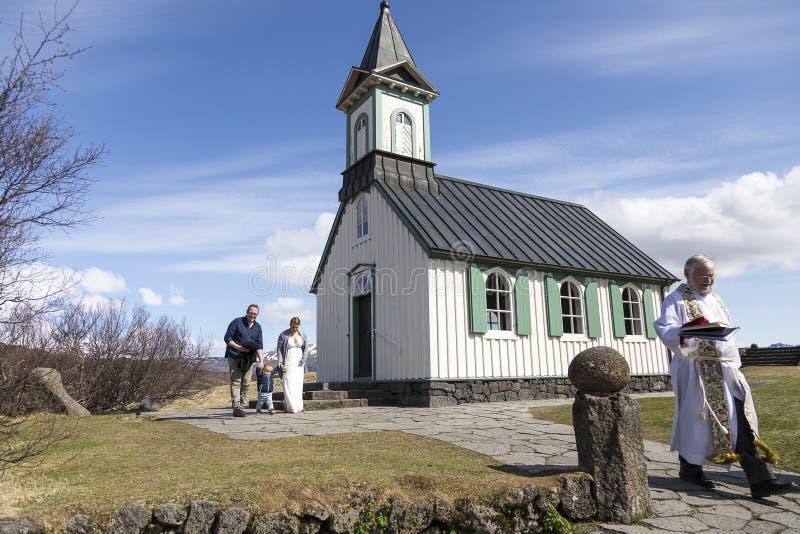 Sacerdote y pareja sonrientes con el pequeño niño que sale de la iglesia de Thingvallakirkja después de la boda muy íntima fotografía de archivo