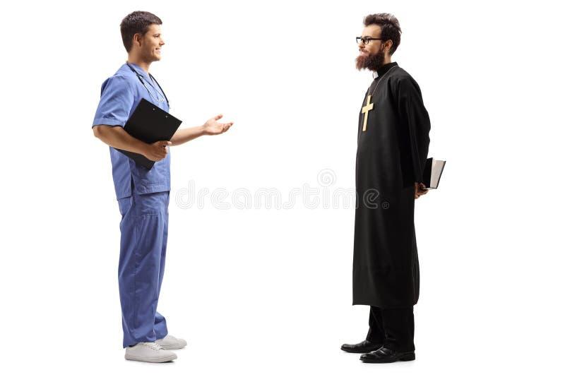 Sacerdote y un doctor de sexo masculino que tiene una conversación fotografía de archivo libre de regalías