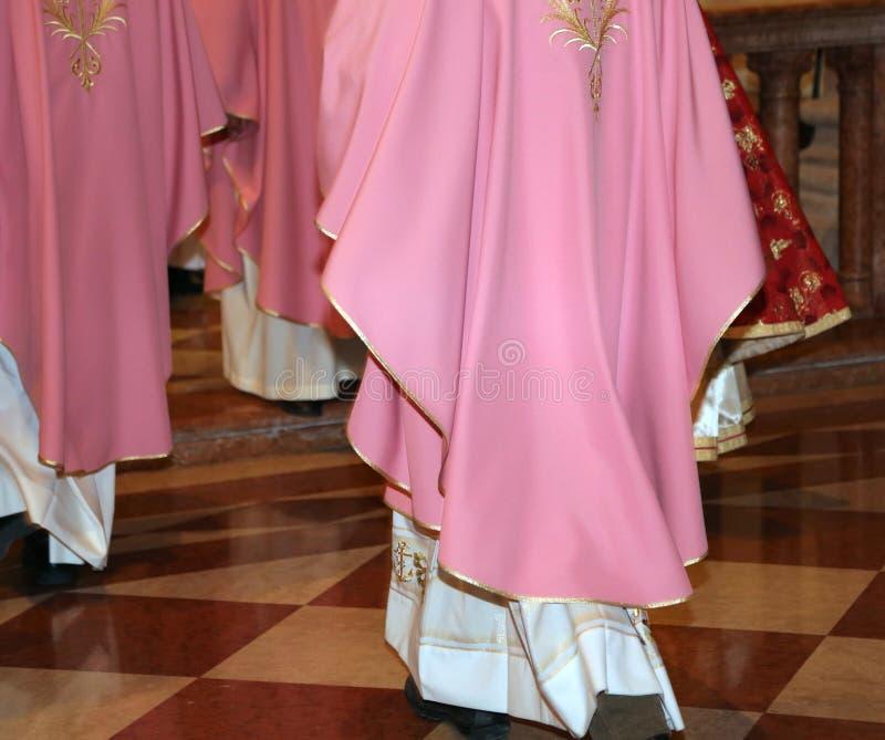 Sacerdotes con la sotana en iglesia durante la misa santa imágenes de archivo libres de regalías