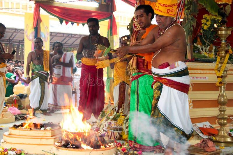 Sacerdotes que hacen el ofrecimiento en la ceremonia india del templo imagen de archivo