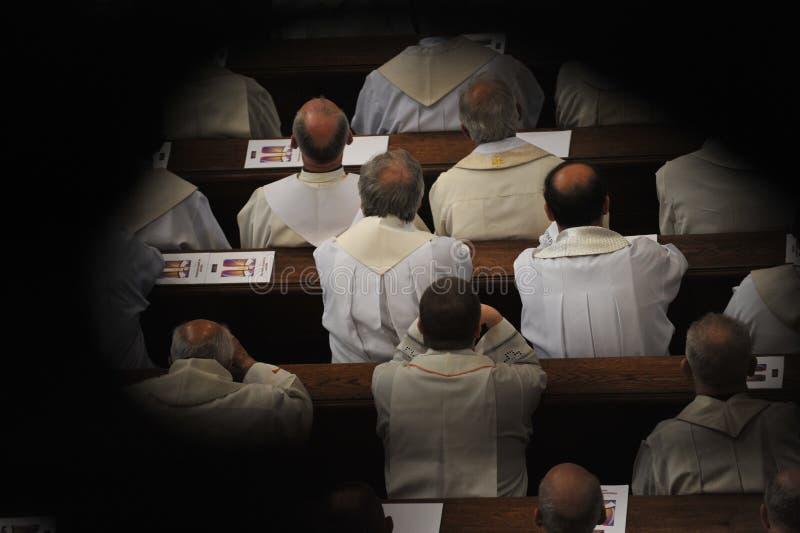 Sacerdotes que se sientan en iglesia fotos de archivo