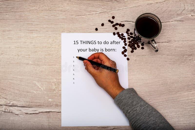 Sachen des Titels 15 zu tun, nachdem Ihr Baby geboren ist Weißes Blatt A4 auf einem hölzernen Hintergrund Ein Tasse Kaffee stockbild