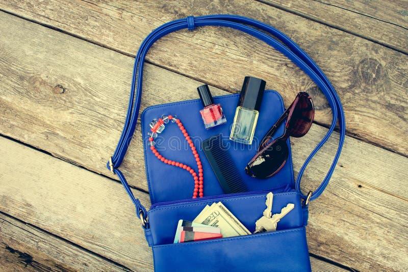 Sachen von offenem Damengeldbeutel Kosmetik, Geld und Frauen ` s Zubehör fielen aus blauer Handtasche heraus lizenzfreies stockbild