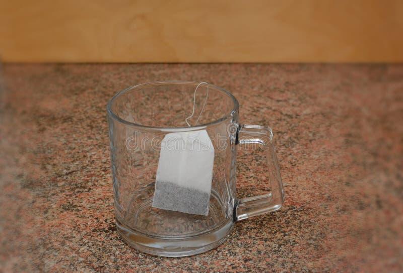 Sachet à thé dans une tasse en verre transparente préparée pour des feuilles de thé images libres de droits