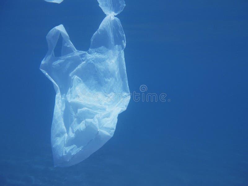 Sachet en plastique flottant dans la mer Ambiant pollué Réutilisez image libre de droits