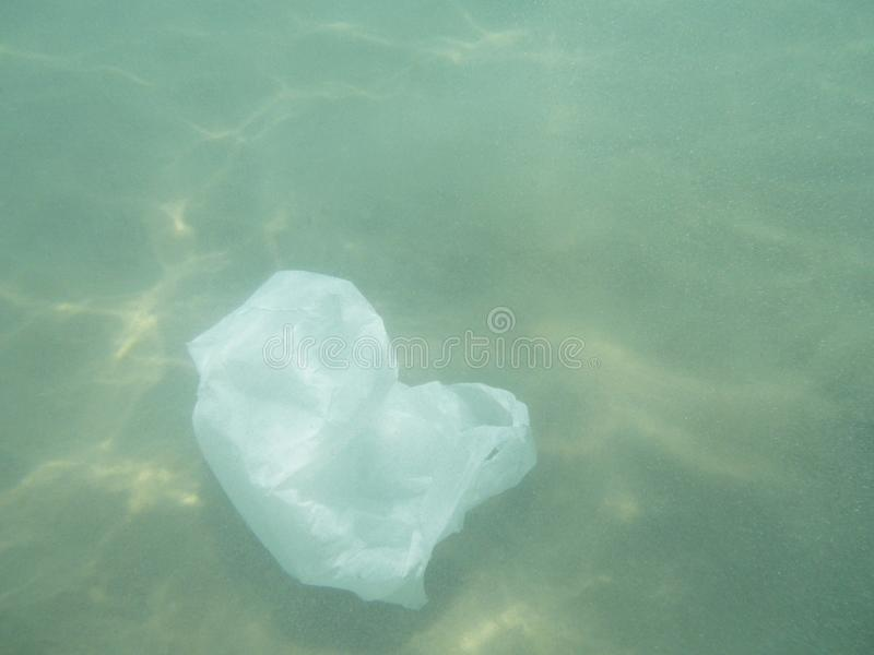 Sachet en plastique flottant dans la mer Ambiant pollué Recycl photographie stock