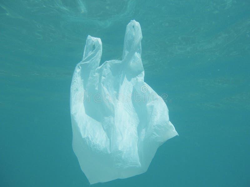 Sachet en plastique flottant dans la mer Ambiant pollué Recycl photographie stock libre de droits
