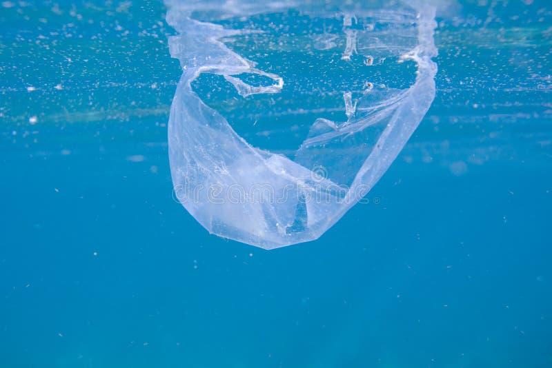 Sachet en plastique en mer bleue Déchets en photo d'eau du fond de mer Eau de mer bleue avec les déchets en plastique Probl?me d' photographie stock libre de droits