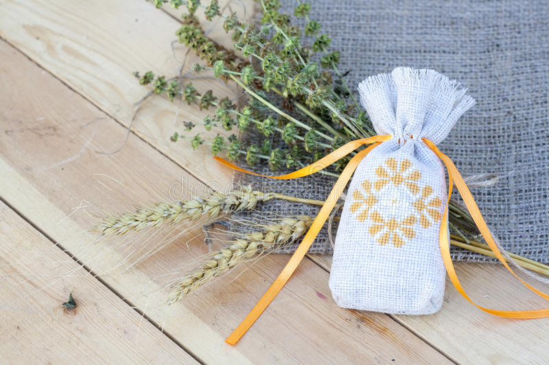Sachet with ukrainian embroidery, sheaf of wheat and dried herbs. On wooden background stock images