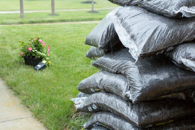 Sachets en plastique empilés de paillis et de fleurs sous la pluie images stock