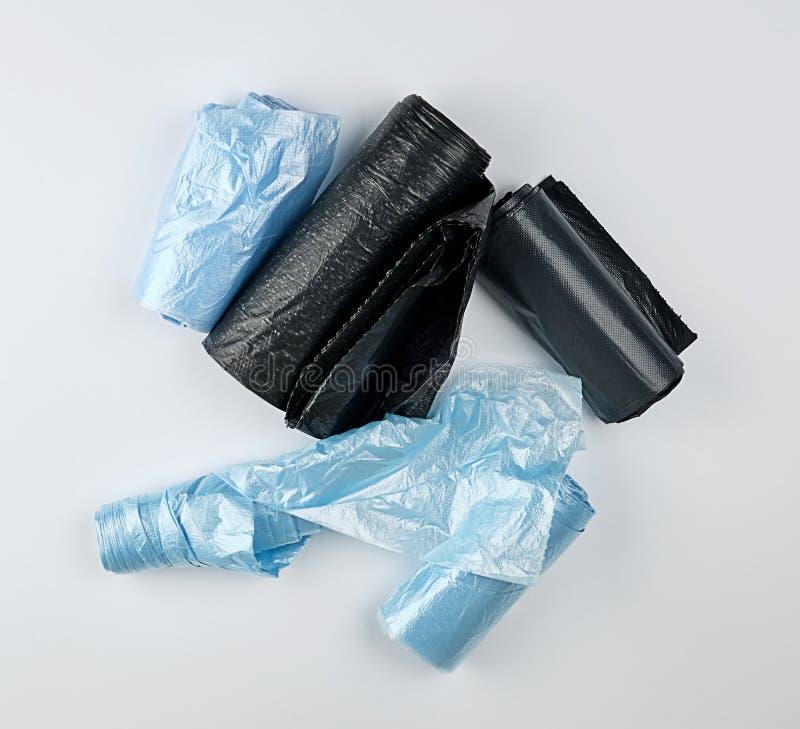 sachets en plastique noirs et bleus pour la poubelle sur un fond blanc photo stock