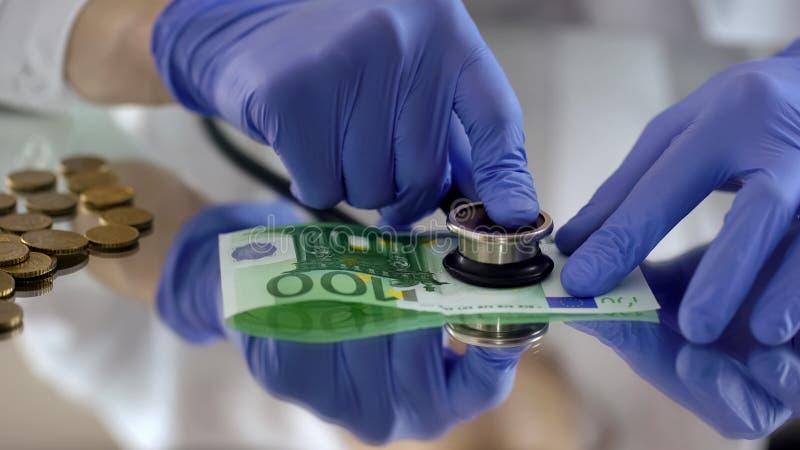 Sachverständige überprüfende Eurobanknote mit Stethoskop, Devisenmarkt lizenzfreies stockfoto