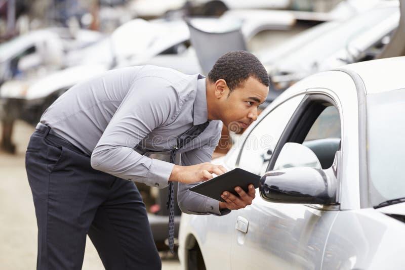 Sachverständiger, der Digital-Tablet in der Auto-Wrack-Inspektion verwendet lizenzfreies stockbild
