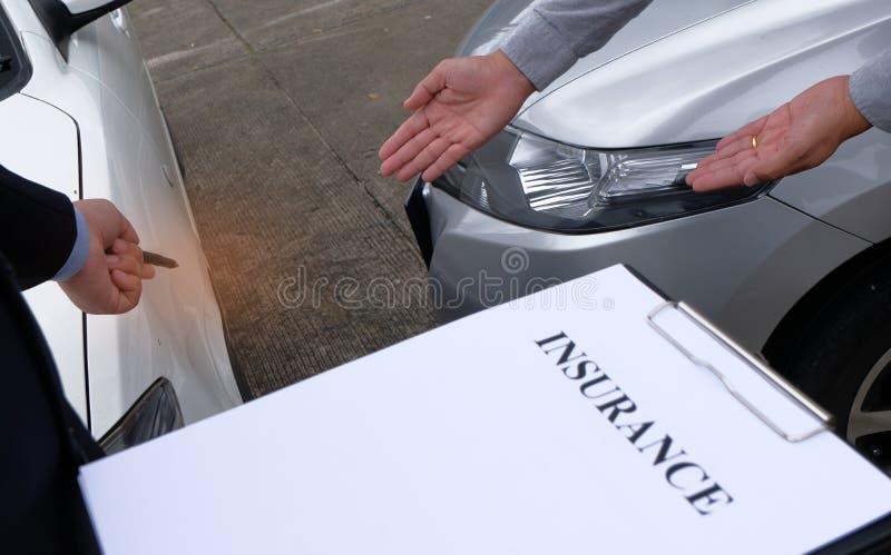 Sachverständiger-Versicherungsagent Inspecting Damaged Car stockfotografie