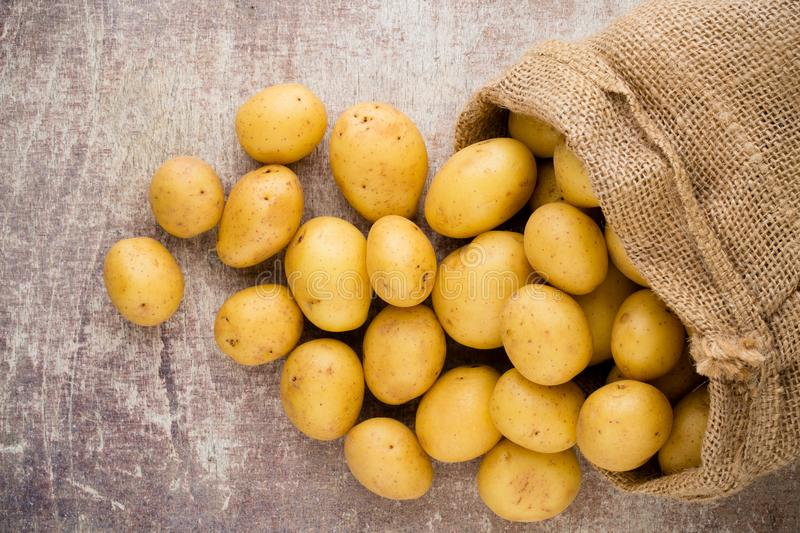 Sack of fresh raw potatoes on wooden background, top view. stock photos