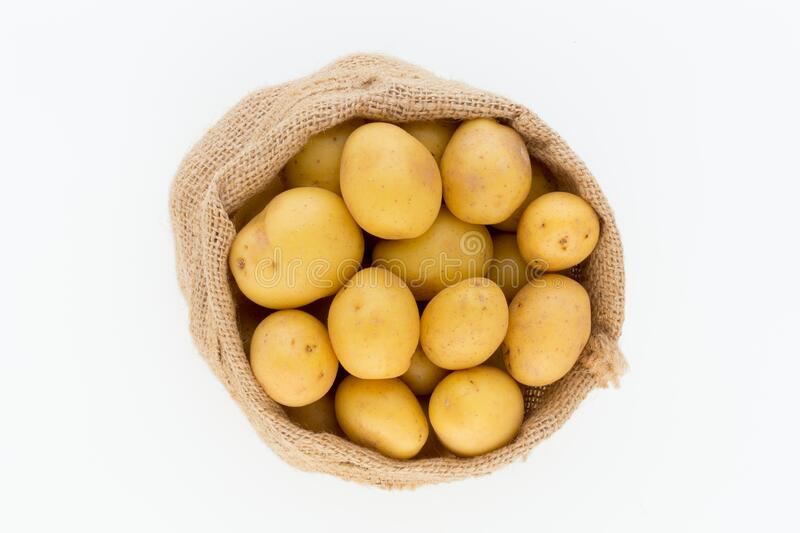 Sack of fresh raw potatoes on wooden background, top view.  royalty free stock images