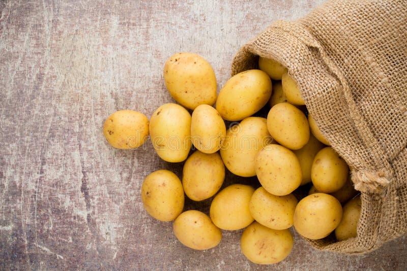 Sack frische rohe Kartoffeln auf hölzernem Hintergrund, Draufsicht lizenzfreie stockbilder