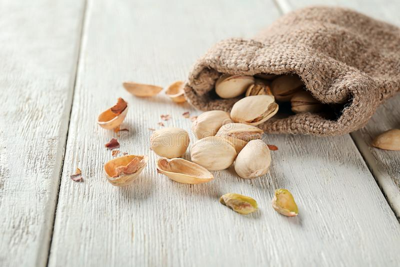Sack and scattered pistachio nuts on white wooden table stock photography