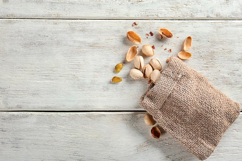 Sack and scattered pistachio nuts on white wooden table stock image