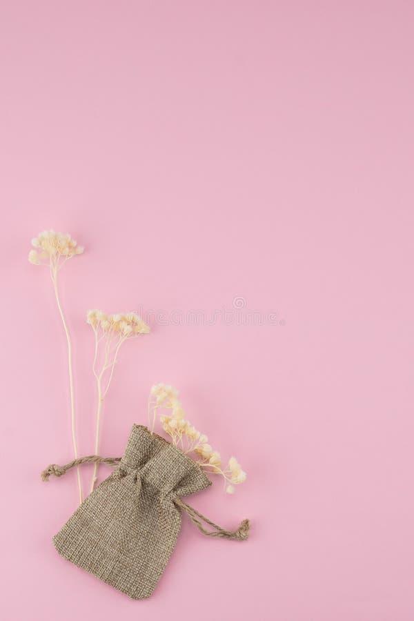 Sackcloth τσάντα με τα άσπρα ξηρά λουλούδια στοκ εικόνες