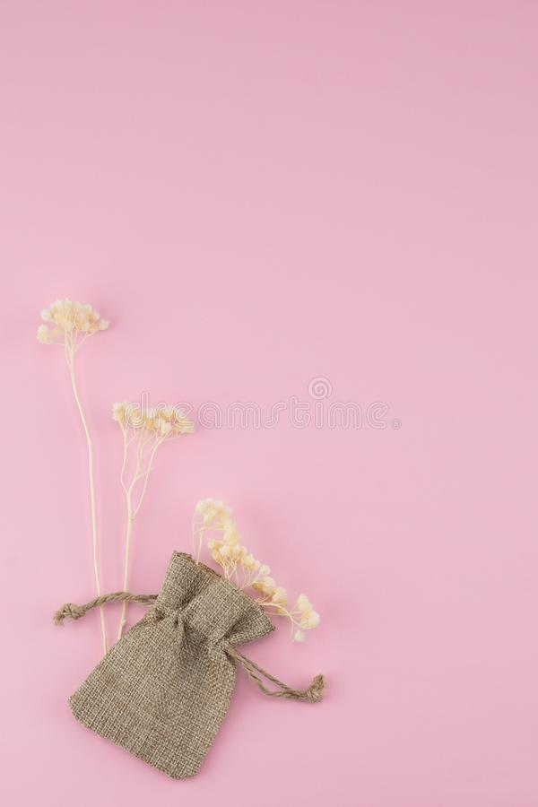 Sackcloth bag with white dried flowers. On pastel pink background with copy space stock images