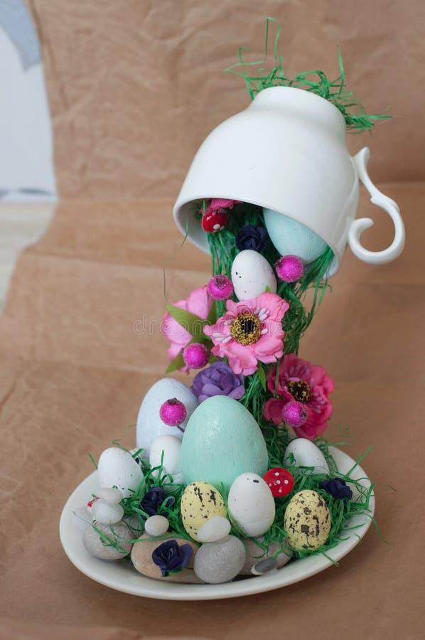 Σπιτικό κέικ σε μια φωλιά από την πλαστή πράσινη χλόη και αυγά Πάσχας που απομονώνονται sackcloth στη σύσταση Ευτυχής ανθοδέσμη Π στοκ φωτογραφίες