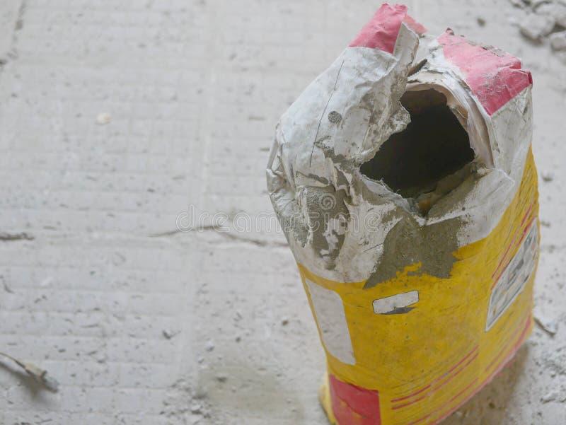 Saco aberto de cimento no chão velho de concreto com todos os ladrilhos antigos removidos, pronto para ser usado para colocar nov fotos de stock