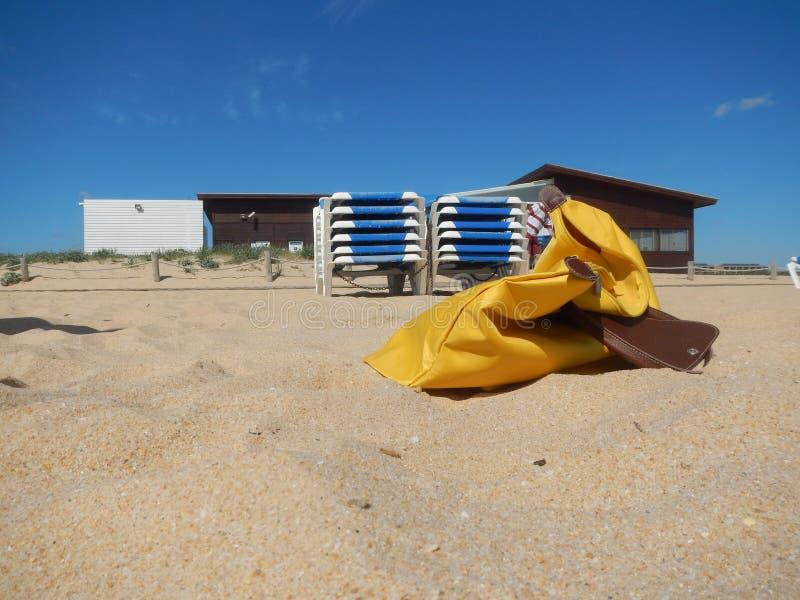 Saco amarelo na areia na praia imagem de stock