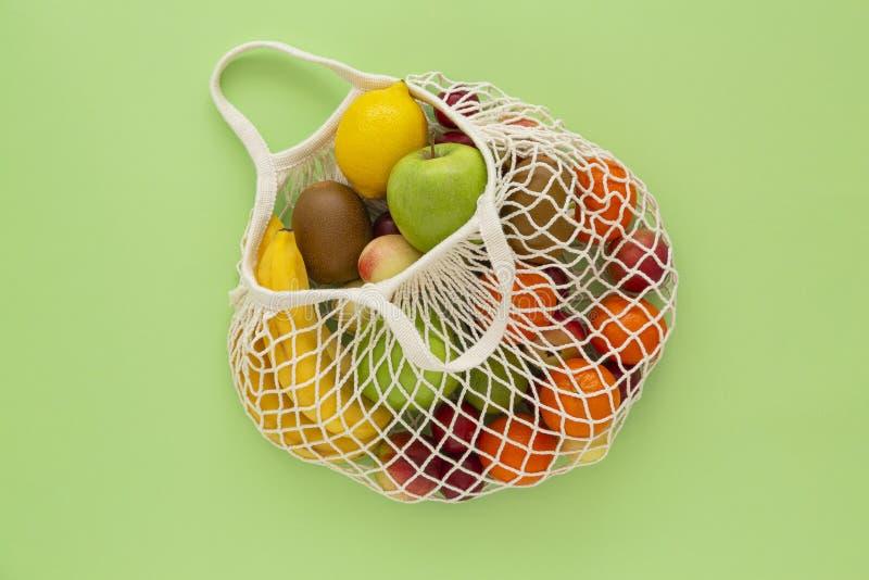 Saco amigável da malha de Eco com fruto orgânico no fundo verde Dieta limpa saudável e desintoxicação comer Frutos do ver?o imagens de stock royalty free