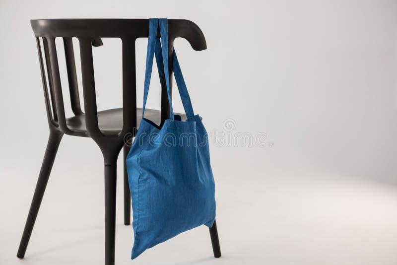 Saco azul que pendura em uma cadeira preta imagem de stock