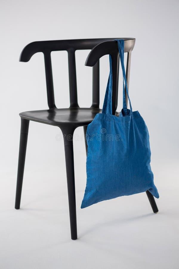 Saco azul que pendura em uma cadeira preta fotografia de stock royalty free