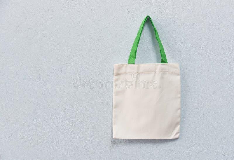 Saco blanco de las compras del paño del bolso del eco de la tela de la lona del totalizador en fondo de la pared foto de archivo