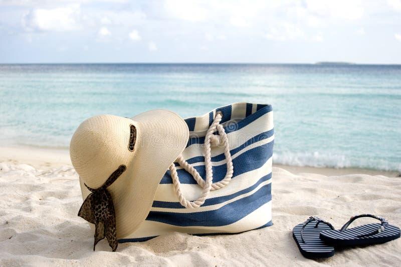 Saco, chapéu e flip-flops na praia fotografia de stock royalty free
