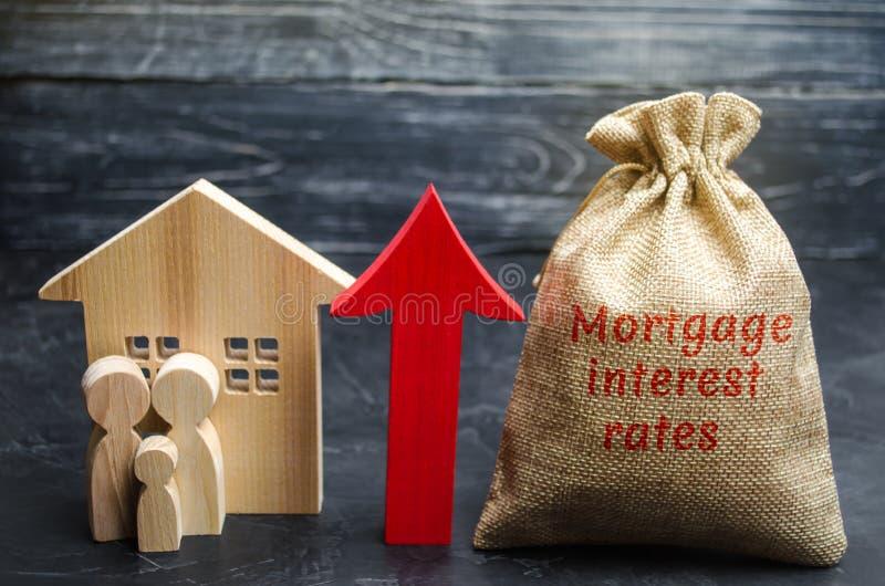 Saco com o dinheiro e as taxas de juros hipotecários da palavra e acima seta com família e casa Levantando taxas hipotecárias e i foto de stock royalty free