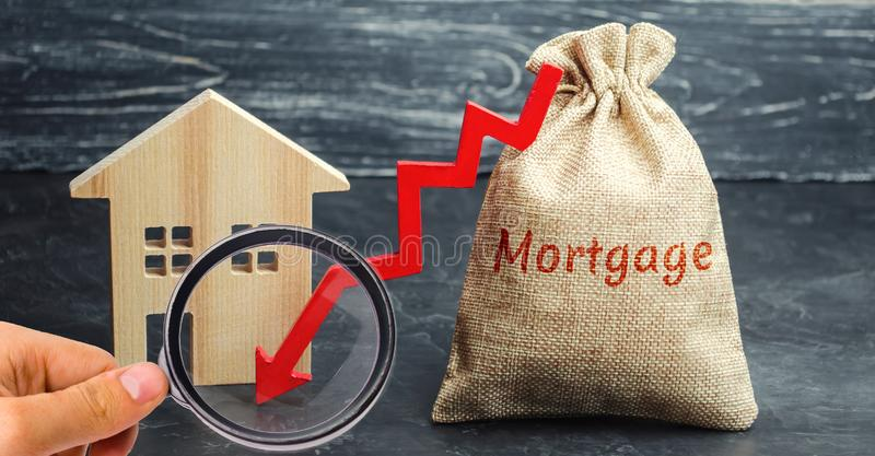 Saco com o dinheiro e a hipoteca da palavra e seta a tragar e abrigar Baixo interesse nas hipotecas Reduzindo pagamentos de inter foto de stock
