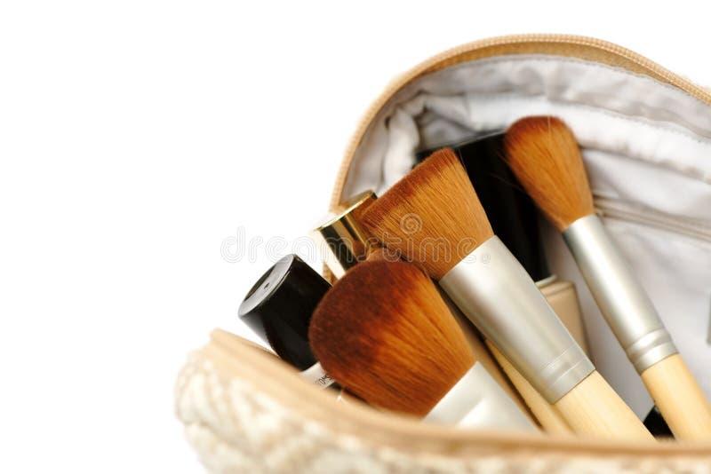 Saco cosmético aberto com escovas da composição e um grupo de cosméticos fotos de stock