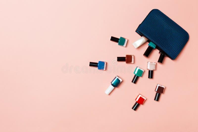Saco cosmético da mulher com tratamento de mãos e pedicure, vernizes brilhantes do gel no fundo cor-de-rosa com espaço da cópia p imagem de stock